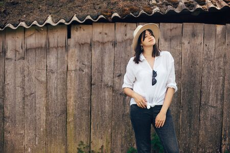 Hipster girl in white casual outfit posing on background of old wooden cabin in mountains. Stylish woman in hat standing near old house. Atmospheric moment, space for text