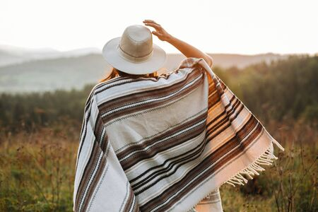 Stylish boho girl walking in sunny light at atmospheric sunset in meadow. Happy hipster woman in poncho and hat enjoying traveling in evening mountains. Space for text