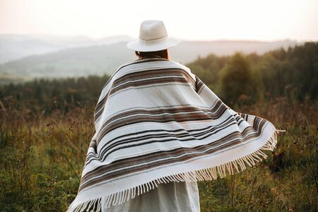 Happy hipster woman in poncho and hat enjoying traveling in evening mountains. Stylish boho girl walking in sunny light at atmospheric sunset in meadow. Space for text