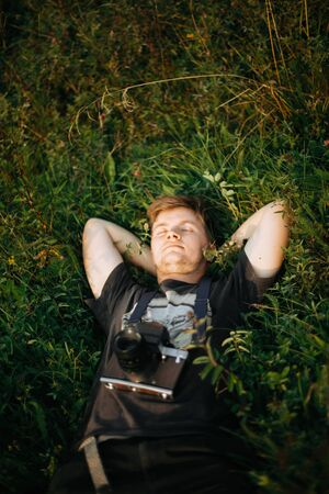 Stylish hipster man with film photo camera lying in green grass and relaxing in sunny meadow at atmospheric sunset. Handsome guy resting in nature and enjoying evening in mountains