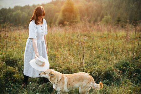 Stylish boho girl playing with her cute dog in grass and wildflowers in sunny meadow in mountains at sunset. Traveling together with pets. Young woman putting hat on golden dog Standard-Bild
