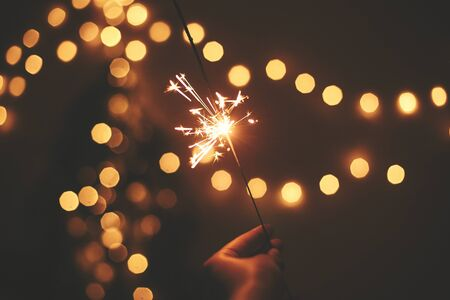 Happy New Year. Glowing sparkler in hand on background of golden christmas tree lights, celebration in dark festive room. Space for text.   Fireworks burning in hand. Happy Holidays Stockfoto