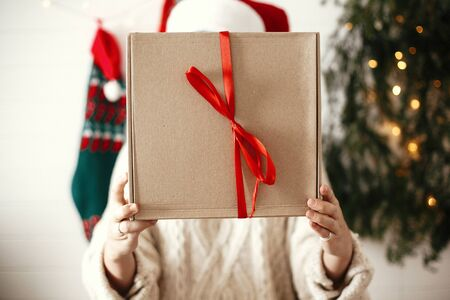 Simple christmas gift box with red ribbon in hands of stylish happy girl in santa hat on background of modern christmas tree, lights and stockings. Merry Christmas and Happy holidays