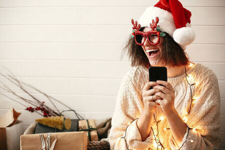 Stylish happy girl in festive glasses with reindeer horns holding phone and smiling in christmas lights. Young hipster woman in santa hat holding smartphone and laughing in christmas room Stock fotó