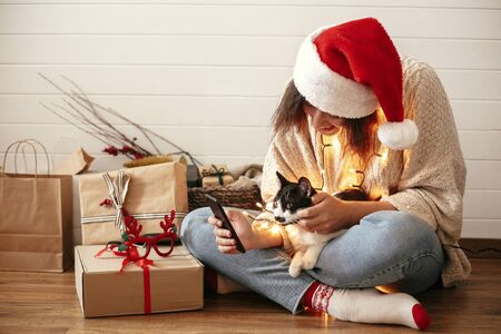 Stylish happy girl in santa hat with cute cat looking at phone screen on background of festive christmas lights and  presents. Young hipster woman hugging kitty with funny emotions