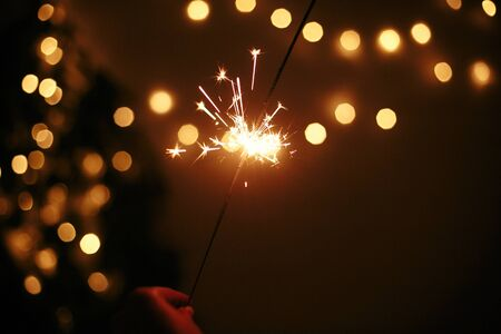 Hand holding glowing sparkler on background of golden christmas lights, celebrating in dark festive room. Space for text. Happy New Year eve party. Happy Holidays. Fireworks burning in hand