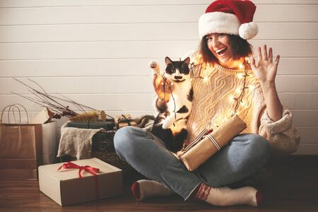 Happy Holidays. Stylish happy girl in santa hat  and cute cat waving hand and paw in festive christmas lights on background of modern presents. Young hipster woman playing with kitty.