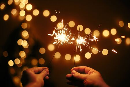 Hands holding glowing sparklers in on background of golden christmas lights, couple celebrating in dark festive room. Happy New Year. Space for text. Fireworks burning in hands