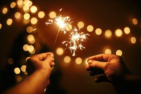 Gloeiende sterretjes in handen op de achtergrond van gouden kerstboomlichten, paar vieren in donkere feestelijke kamer. Gelukkig nieuwjaar. Ruimte voor tekst. Vuurwerk branden in handen. Prettige Feestdagen Stockfoto