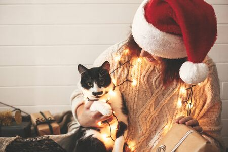 Stylish happy girl in santa hat playing with cute cat in festive christmas lights on background of modern room with presents. Young hipster woman in cozy sweater hugging kitty and smiling