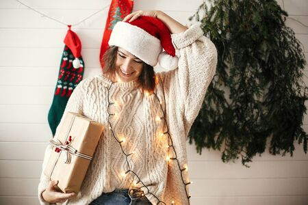 Stylish happy girl in santa hat and cozy sweater holding christmas gift box on background of modern christmas tree, lights and stockings. Young hipster woman holding present and smiling