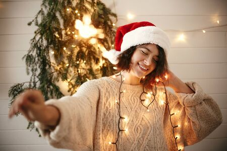 Stylish happy girl in santa hat holding sparkler on background of modern christmas tree lights in festive room. Happy New Year eve party. Hipster woman with fireworks. Happy Holidays Фото со стока