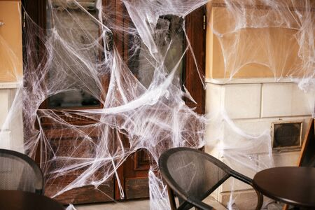 Spooky spider web on building facade in city street, holiday decoration of store fronts. Halloween street decor. Space for text. Trick or treat. Happy halloween. Autumn market Stock fotó