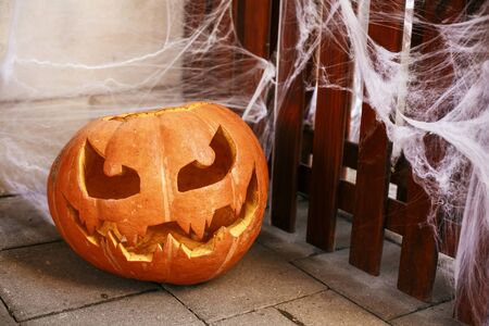 Halloween street decor. Jack o lantern pumpkin and spider web in city street, holiday decor of store fronts and buildings. Autumn market in town. Space for text. Trick or treat. Happy halloween Stock fotó