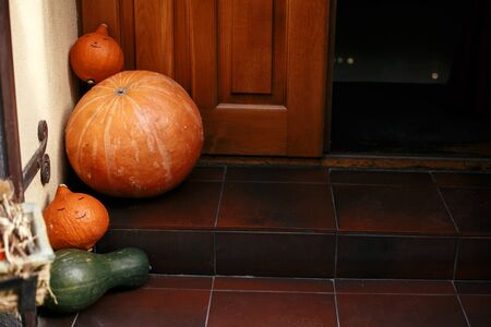 Pumpkins and squash in city street, holiday decorations store fronts and buildings. Halloween street decor. Space for text. Trick or treat. Happy halloween. Autumn market in town