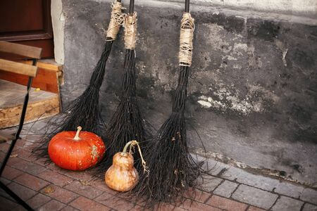 Pumpkins and witch brooms in city street, holiday decoration of store fronts and buildings. Halloween street decor. Space for text. Trick or treat. Happy halloween. Autumn market
