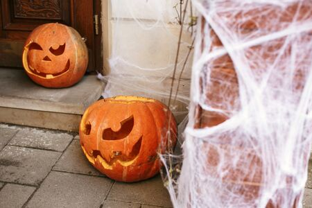 Pumpkins with scary faces and spider web in city street, holiday decoration of store fronts and buildings. Halloween street decor. Space for text. Trick or treat. Happy halloween