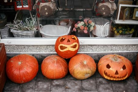 Halloween street decor. Jack o lantern pumpkins on city street, holiday decor of store fronts and buildings. Autumn market in town. Space for text. Trick or treat. Happy halloween
