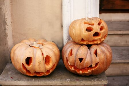 Pumpkins with scary faces in city street, holiday decoration of store fronts and buildings. Halloween street decor. Space for text. Trick or treat. Happy halloween. Autumn market in town
