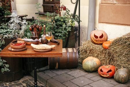 Pumpkins with scary faces on hay at cafe table, holiday decoration of store fronts and buildings. Halloween street decor. Space for text. Trick or treat. Happy halloween. Autumn market in town.