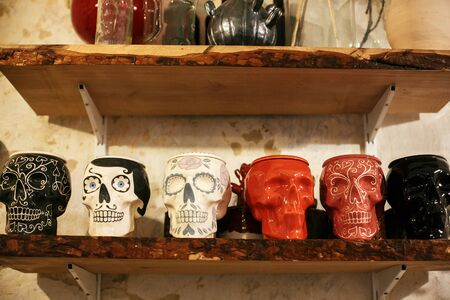 Colorful skulls in city street, halloween street decor. Ceramic painted skulls for Day of Dead on shelf, mexican tradition, Dia de los Muertos. Space for text. Happy halloween