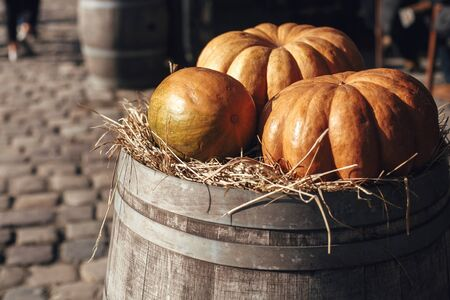 Pumpkin on barrel with hay in city street, holiday decorations store fronts and buildings. Halloween street decor. Space for text. Trick or treat. Happy halloween. Autumn market in town Stok Fotoğraf