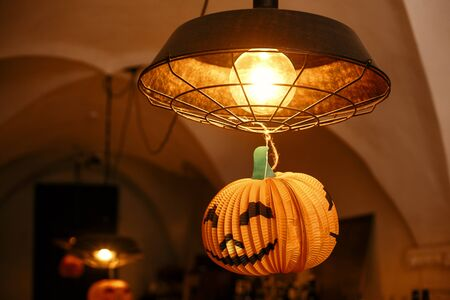 Jack o lantern pumpkin hanging on lamp in city street, holiday decoration of store fronts. Halloween street decor. Space for text. Happy halloween. Autumn market Stock fotó