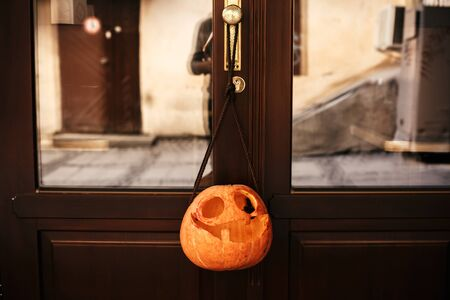 Trick or treat. Pumpkins with scary faces in city street, holiday decoration of store fronts and buildings. Halloween street decor. Space for text. Happy halloween. Autumn market in town Stock fotó
