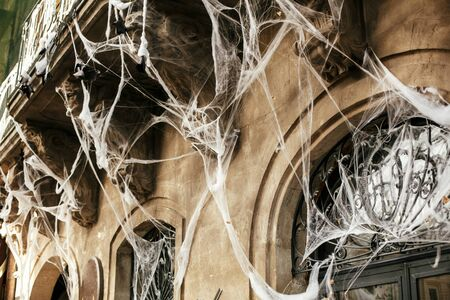 Halloween street decor. Spooky spider web on building facade in city street, holiday decoration of store fronts.  Space for text. Trick or treat. Happy halloween. Autumn market