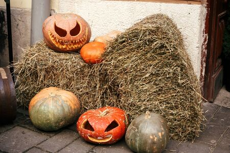 Pumpkins with scary faces on hay in city street, holiday decoration of store fronts and buildings. Halloween street decor. Space for text. Trick or treat. Happy halloween. Autumn market in town. Stock fotó