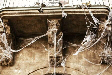 Spooky spider web and bats on building facade in city street, holiday decoration of store fronts. Halloween street decor. Space for text. Trick or treat. Happy halloween. Autumn market