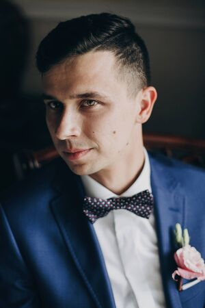 Stylish groom in blue suit, with bow tie and boutonniere with pink rose posing near window in hotel room. Morning preparation before wedding ceremony 스톡 콘텐츠 - 128326648