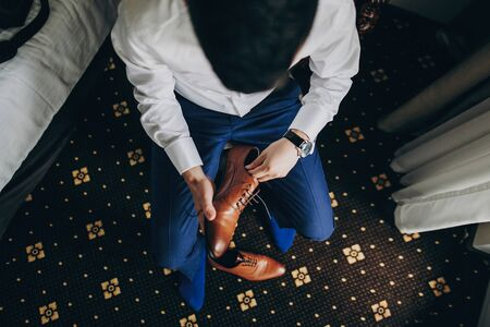 Stylish groom in blue suit putting on brown shoes near window in hotel room, top view. Morning preparation before wedding ceremony. Man getting ready before luxury event Stockfoto
