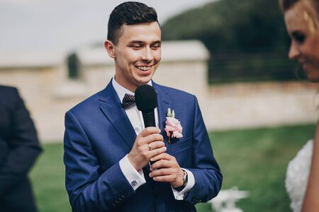 Stylish groom pronouncing vow to his beautiful bride during matrimony. Groom pronouncing speech and holding microphone. Beautiful wedding ceremony in summer park or garden 스톡 콘텐츠