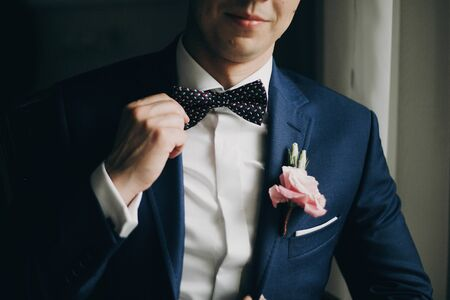 Stylish groom in blue suit with boutonniere with pink rose holding bow tie and posing near window in hotel room. Morning preparation before wedding ceremony 스톡 콘텐츠