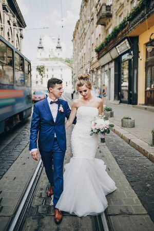 Stylish happy bride and groom walking and smiling in sunny city street. Gorgeous wedding couple of newlyweds embracing outdoors. Romantic moment