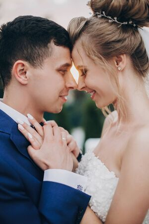 Stylish happy bride and groom posing in warm sunset light at wedding reception outdoors. Gorgeous wedding couple of newlyweds  embracing in evening sunlight Фото со стока - 128326674