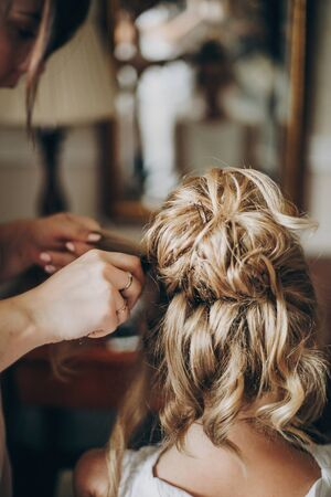 Beautiful happy bride getting her hair done by professional hair stylist in hotel room. Morning preparation before wedding ceremony. Modern hairbead