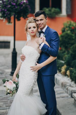 Stylish bride and groom posing in sunny european city street. Gorgeous wedding couple of newlyweds embracing at old buildings. Romantic moment