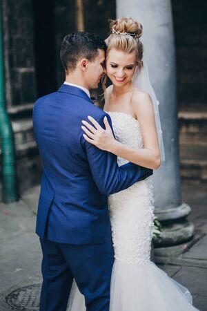 Stijlvolle bruid en bruidegom knuffelen zachtjes in de zonnige Europese stadsstraat. Schitterend huwelijkspaar van jonggehuwden die in oude gebouwen omhelzen. Romantisch moment