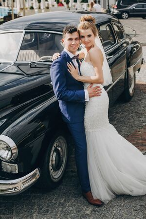 Stylish happy bride and groom posing at old retro car. Gorgeous wedding couple of newlyweds smiling and hugging after wedding ceremony. Romantic moment