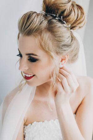 Elegante novia feliz sonriendo y posando en luz suave junto a la ventana en la habitación del hotel. Preparación de la mañana antes de la ceremonia de la boda. Retrato de novia hermosa Foto de archivo