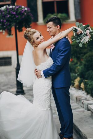 Stylish bride and groom posing and smiling in sunny european city street. Gorgeous wedding couple of newlyweds embracing at old buildings. Romantic moment 스톡 콘텐츠