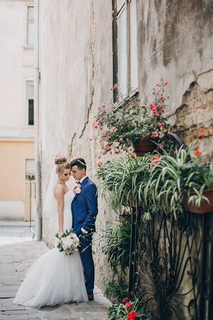 Stylish happy bride and groom posing in old european city street. Gorgeous wedding couple of newlyweds embracing  outdoors. Romantic moment Фото со стока - 128326683