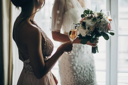 Cropped view of stylish bride holding modern wedding bouquet and bridesmaid toasting with champagne glass near window in hotel room. Morning preparation before wedding ceremony