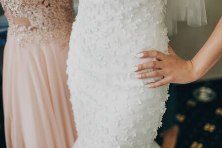 Stylish bride holding hand with pink nails manicure on modern dress, getting ready in hotel room. Morning preparation before wedding ceremony.