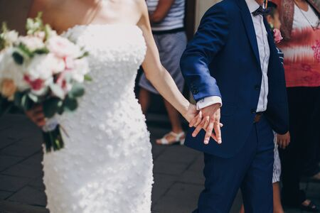 Stylish bride with bouquet and groom walking in sunny european city street and holding hands closeup. Gorgeous wedding couple of newlyweds embracing outdoors. Romantic moment 스톡 콘텐츠