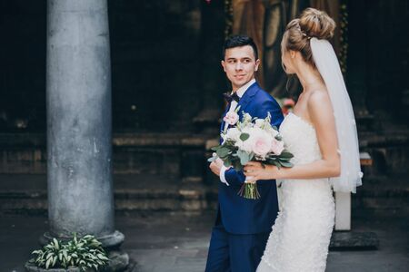 Stylish happy bride and groom walking in sunny european city street. Gorgeous wedding couple of newlyweds embracing in old buildings. Romantic moment Фото со стока - 128326684