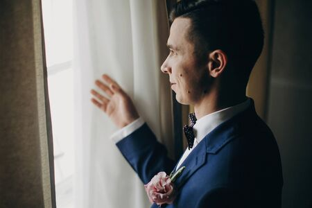 Stylish groom in blue suit, with bow tie and boutonniere with pink rose posing near window in hotel room. Morning preparation before wedding ceremony Фото со стока - 128326685