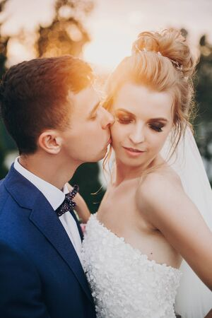 Stylish happy bride and groom kissing in warm sunset light at wedding reception outdoors. Gorgeous wedding couple of newlyweds  embracing in evening sunlight